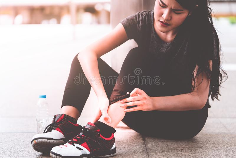 从跑,握她的充满痛苦的亚裔妇女的伤害脚腕 免版税库存照片