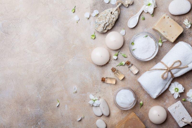 从身体关心和秀丽threatment产品的温泉设置与在石背景顶视图的花 健康和健康概念 图库摄影