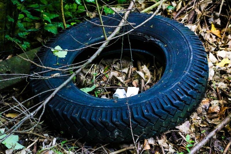从轮子谎言的老破裂的轮胎在垃圾填埋 免版税库存图片