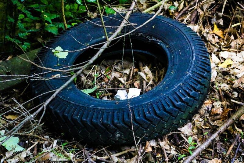 从轮子谎言的老破裂的轮胎在垃圾填埋 免版税库存照片