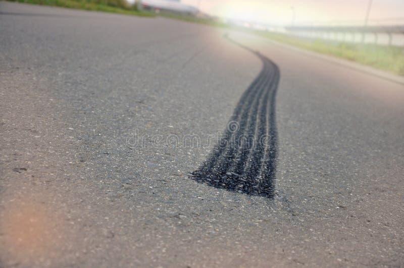 从轮胎的踪影从紧急刹车在沥青 免版税图库摄影