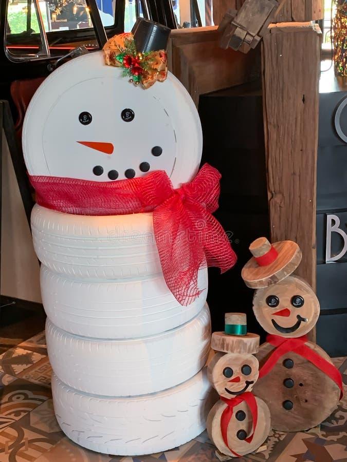从轮胎背景的雪人 免版税库存照片