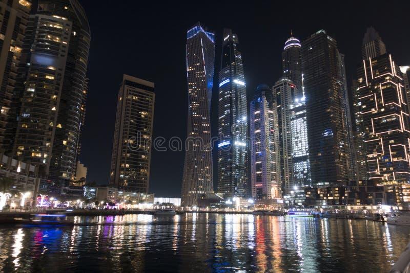 从迪拜小游艇船坞的有启发性摩天大楼在水中夜间反射了 免版税库存图片