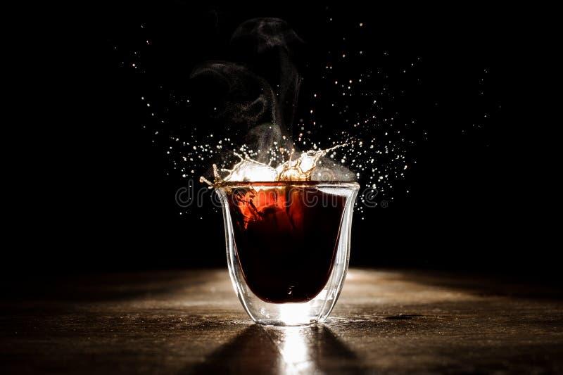 从透明玻璃杯子溢出的热和芳香咖啡 库存图片