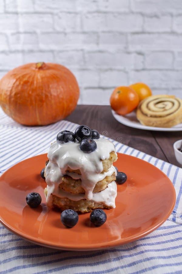 从酸奶干酪的几个自创薄煎饼用蓝莓和酸性稀奶油 自创乳酪油炸馅饼 免版税库存照片