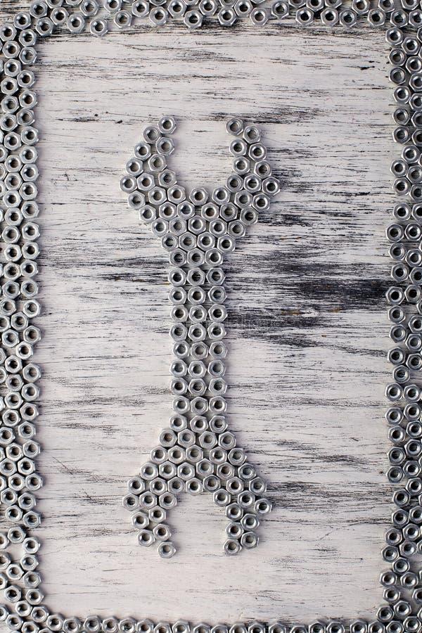 从金属坚果背景的坚果板钳 平的位置 免版税库存照片