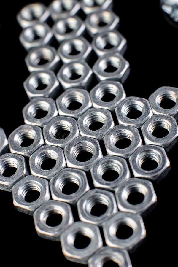 从金属坚果,在黑背景的螺栓的箭头 平的位置 宏指令 库存照片