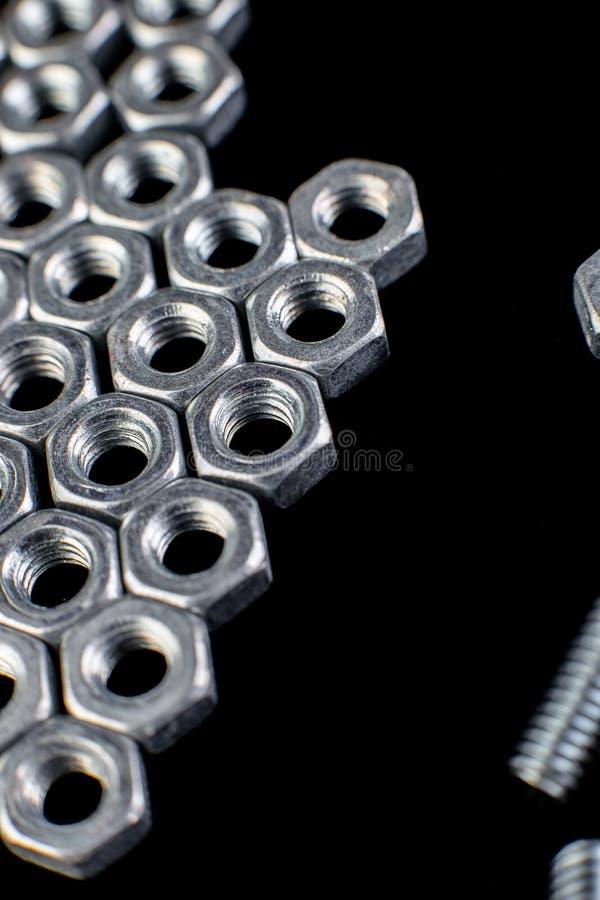 从金属坚果,在黑背景的螺栓的箭头 平的位置 宏指令 免版税库存图片