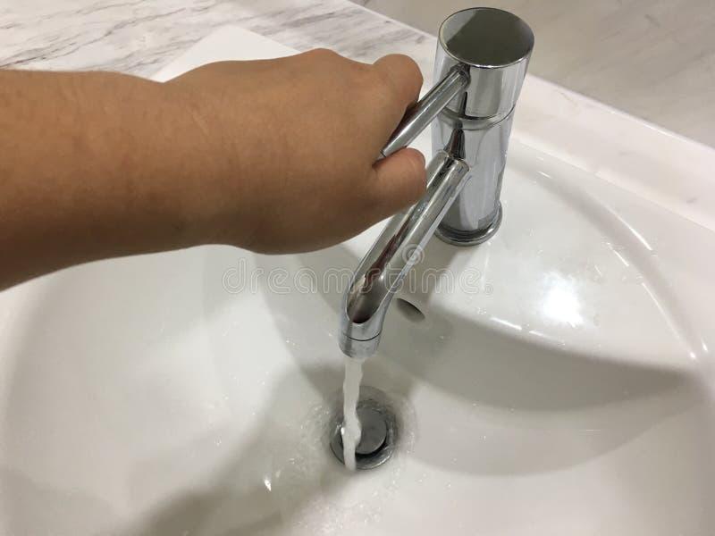 从金属轻拍的水流量在妇女手的水池里面在卫生间里 免版税库存照片