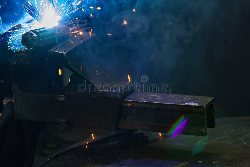 从金属零件焊接的明亮的闪光  复制的地方在烟的黑暗的背景 强光和火花在工作期间  库存图片