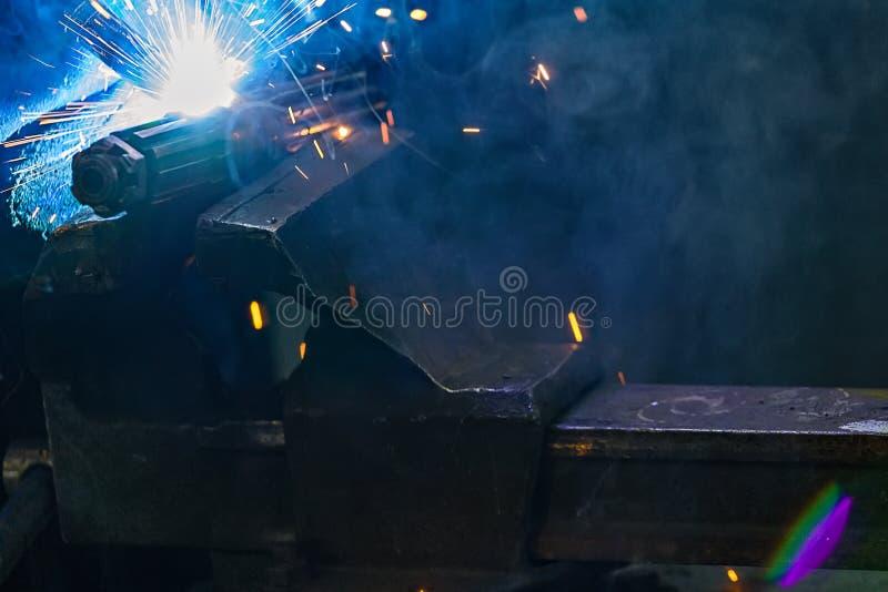 从金属零件焊接的明亮的闪光  复制的地方在烟的黑暗的背景 强光和火花在t期间工作  免版税库存图片