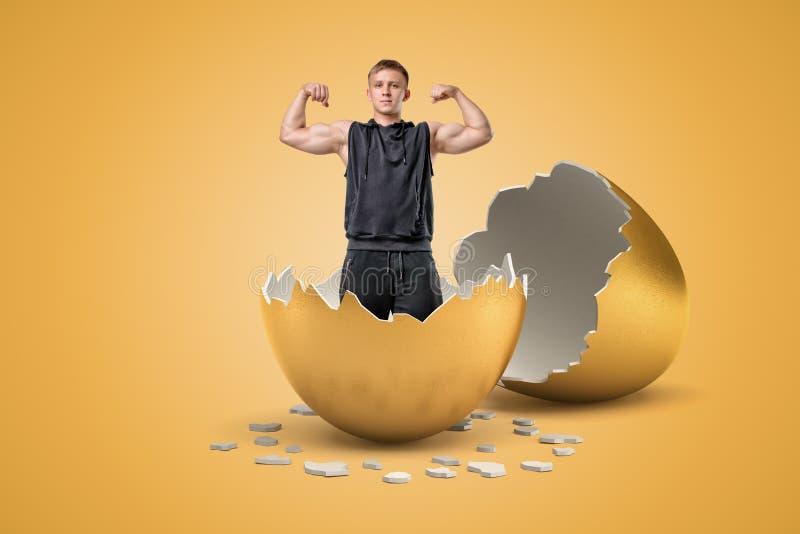 从金黄鸡蛋孵化了举手和显示他的肌肉的年轻适合的人 免版税库存图片