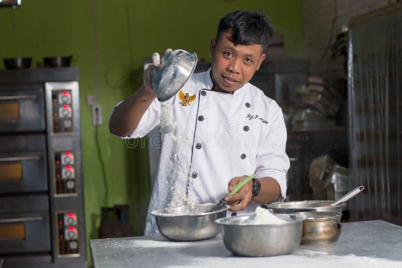 从钢碗的亚洲男性点心师倾吐的面粉在厨房的不锈的桌上 免版税库存照片