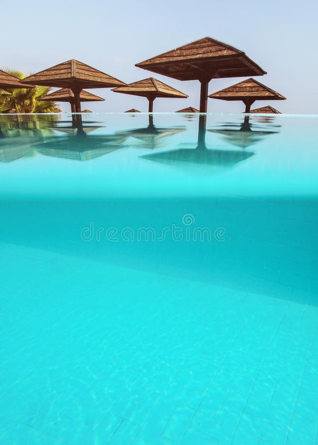 从镇静无限水池看见的木方形的太阳遮阳伞 部分地水下的照片,底部是蓝色砖地-空间为 免版税库存照片