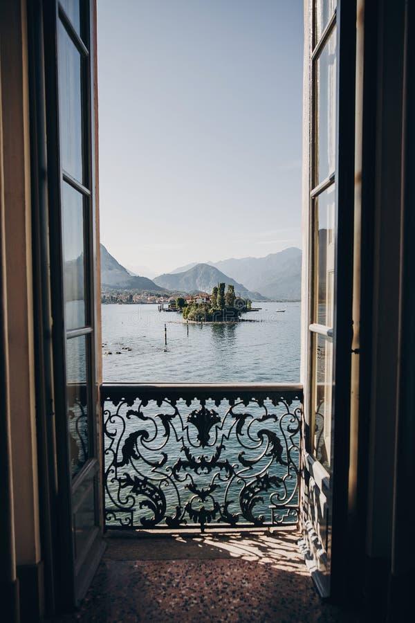 从阳台窗口在拉戈马吉欧雷和Borromean海岛的美丽的景色晴朗的光的,探索的意大利 老建筑学 库存照片