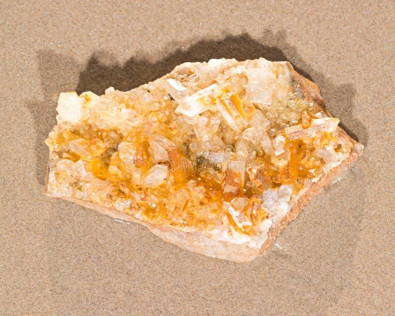 从阿肯色的金黄愈疗者群石英标本在海滩的湿沙子的 库存照片