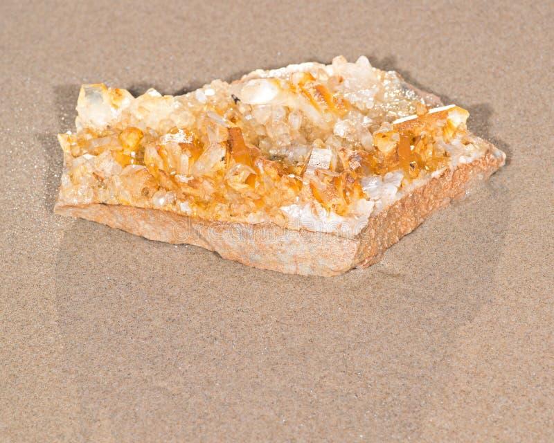 从阿肯色的金黄愈疗者群石英标本在海滩的湿沙子的 免版税库存图片