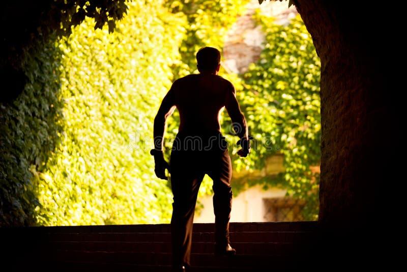 从隧道出来赛跑者的黑剪影  库存照片