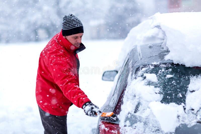 从雪的清洁汽车 清洗汽车挡风玻璃从雪和冰的人在雪风暴以后 免版税图库摄影