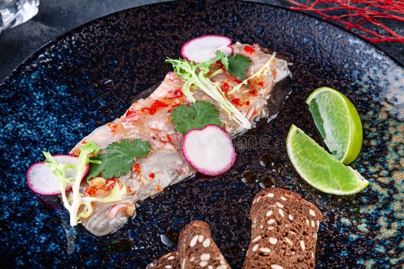 从雪鱼的新和鲜美cebiche 从生鱼片的海鲜盘 与石灰的Ceviche和在黑暗的板材microgreen服务 ?? 免版税库存照片