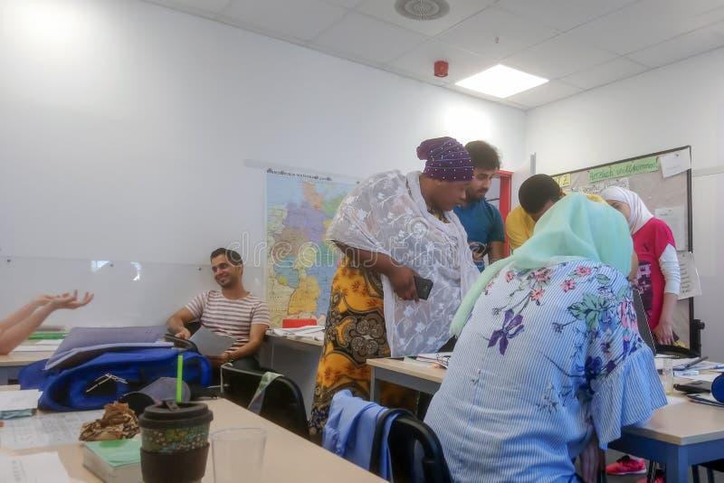 从非洲、亚洲和中东的移民在哈雷萨勒河学会德语在国际学校Inlingua的类, 图库摄影