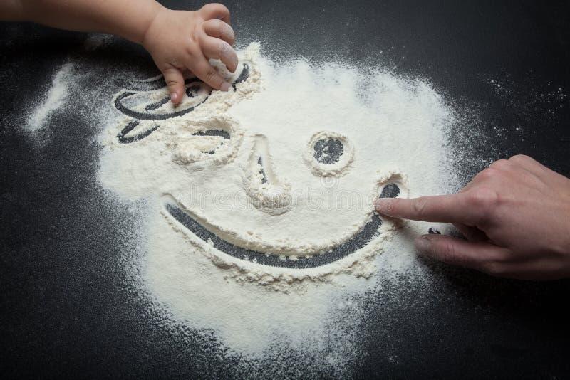 从面粉的面带笑容,画手指妈妈和女儿 免版税库存图片