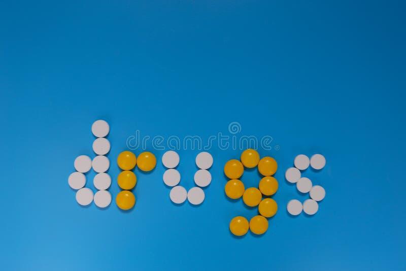 从颜色胶囊的词药物在蓝色背景 顶视图拷贝空间 免版税图库摄影
