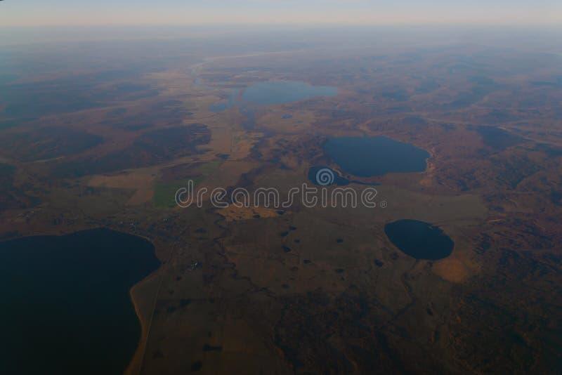 从飞机的窗口的看法对湖和河的天际的山的与森林天的日落的 免版税图库摄影