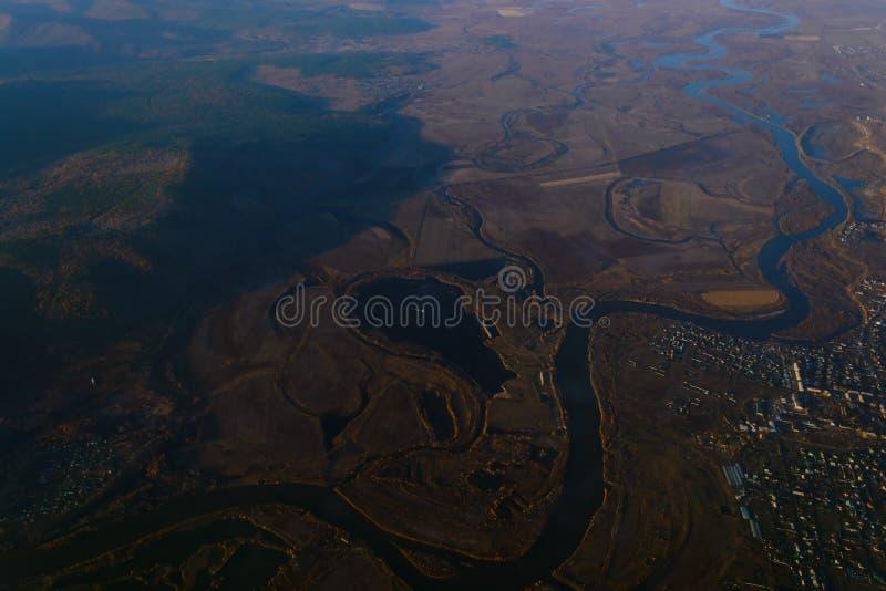 从飞机的窗口的看法对湖和河的天际的山的与森林天的日落的 库存图片