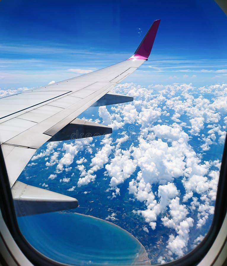 从飞机窗口的天空视图,这是我们将看见美丽的清楚的天空,白色云彩,海和的高观点 免版税库存图片