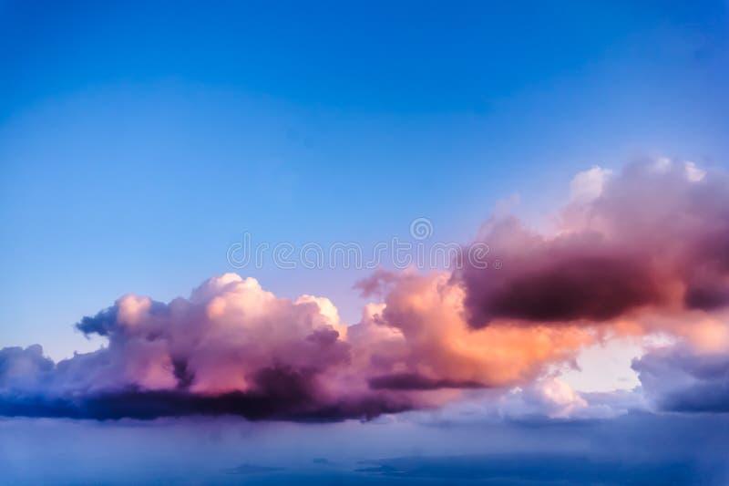 从飞机窗口-白色,紫色和粉红云彩的美丽的景色 免版税图库摄影