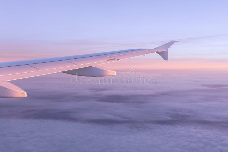 从飞机舷窗的看法在粉色天空与空气云彩和飞机的翼的 库存照片
