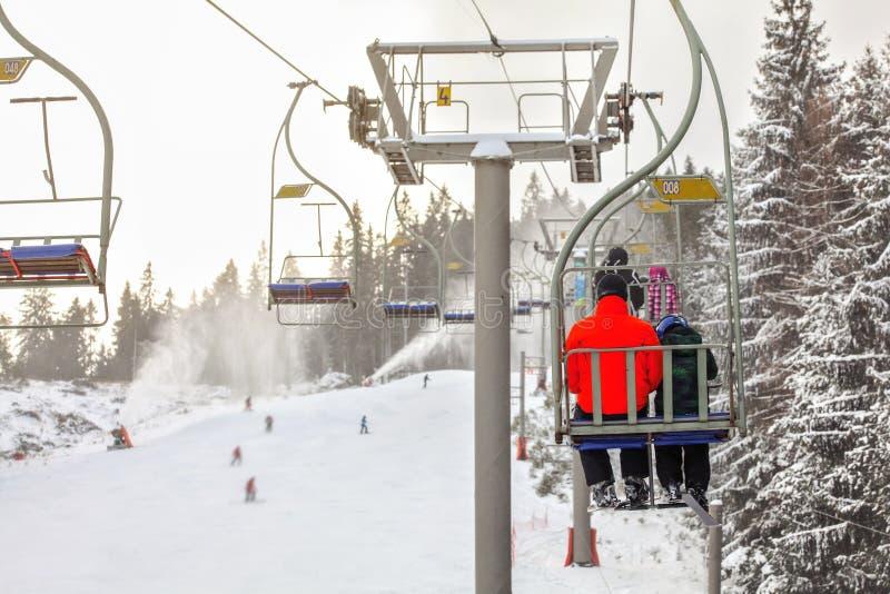 从驾空滑车的看法在滑雪滑雪道,明亮的红色夹克就座的滑雪者在下面前面,被弄脏的人滑雪,活跃snowguns 免版税库存照片