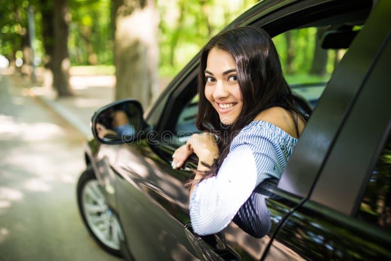 从驾驶汽车的窗口的无忧无虑的妇女微笑假期幸福微笑假日 免版税库存图片