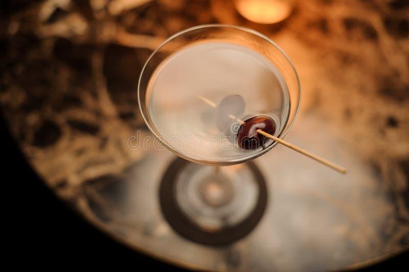 从鸡尾酒上的看法在用装饰的冰冷的玻璃在串身分的莓果在大理石桌上 免版税图库摄影