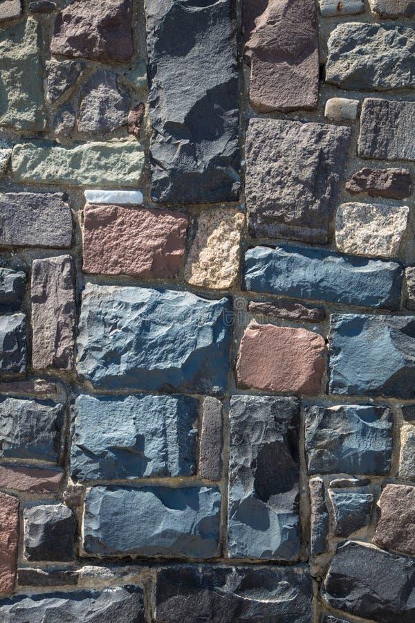 从鹅卵石背景垂直的石墙 免版税库存照片