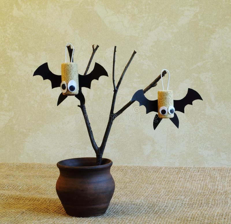 从黄柏的棒和在一个老干燥分支的黑纸板在一种手织的黄麻织品的一个陶瓷花瓶对轻的墙壁 ?? 免版税库存图片