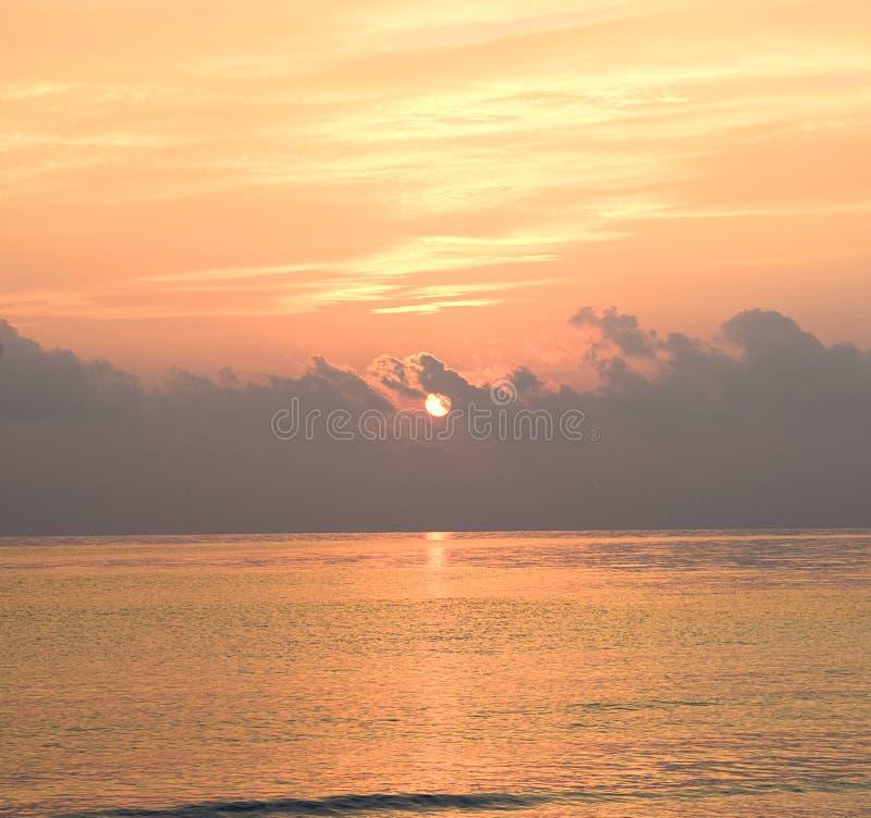 从黑暗的云彩的升起的金黄太阳在海的天际有明媚的阳光和五颜六色的天空的 库存图片