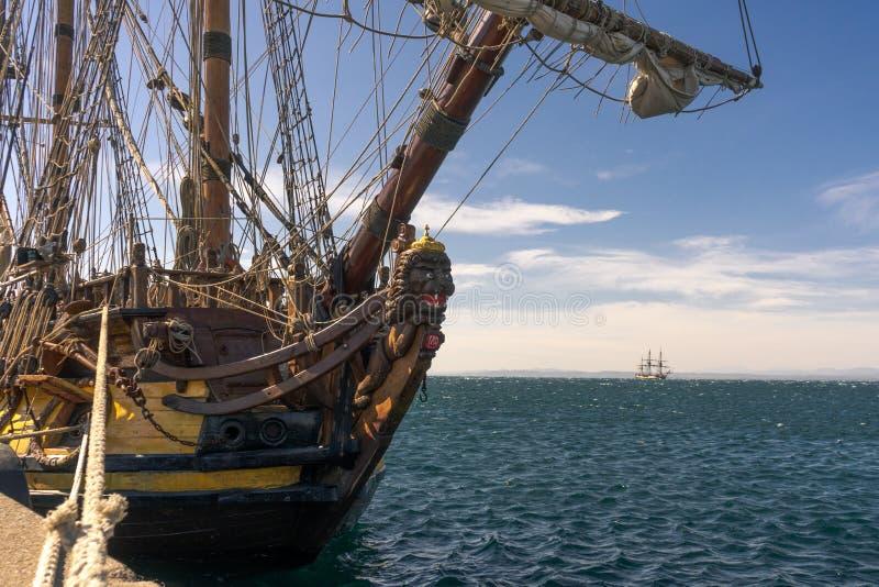 从1703的老风船停住在与等待在背景中的另一艘船的岸 库存图片