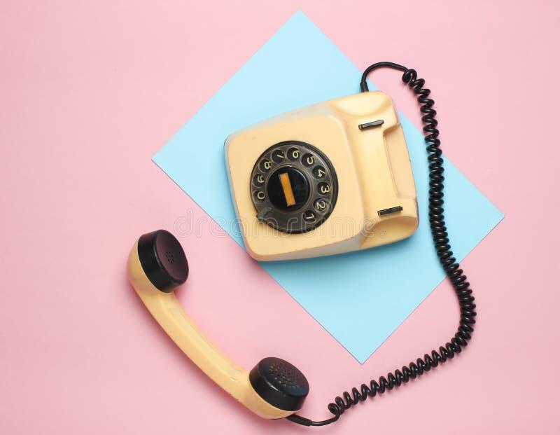 从80s的减速火箭的转台式电话在色的淡色背景 顶视图,简单派 免版税库存图片