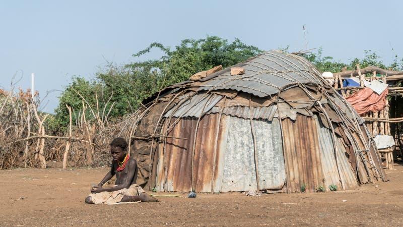 从Dassanech部落的未认出的女孩坐土壤地面,埃塞俄比亚 库存图片