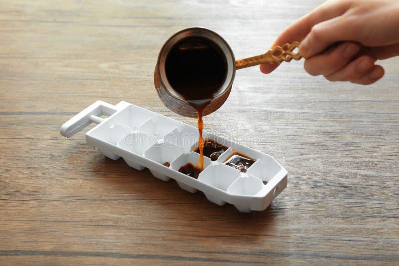 从jezve的妇女倾吐的咖啡到在桌上的冰格里 免版税库存照片