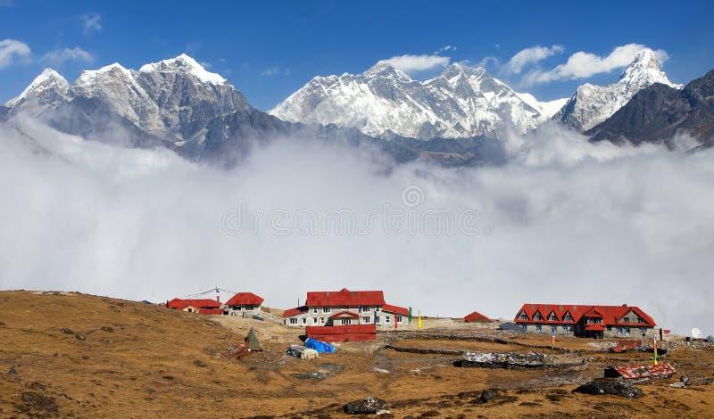 从Kongde的全景珠穆朗玛峰洛子峰和阿玛达布拉姆峰与旅游小屋和美丽的云彩,全国的萨加玛塔 免版税库存图片