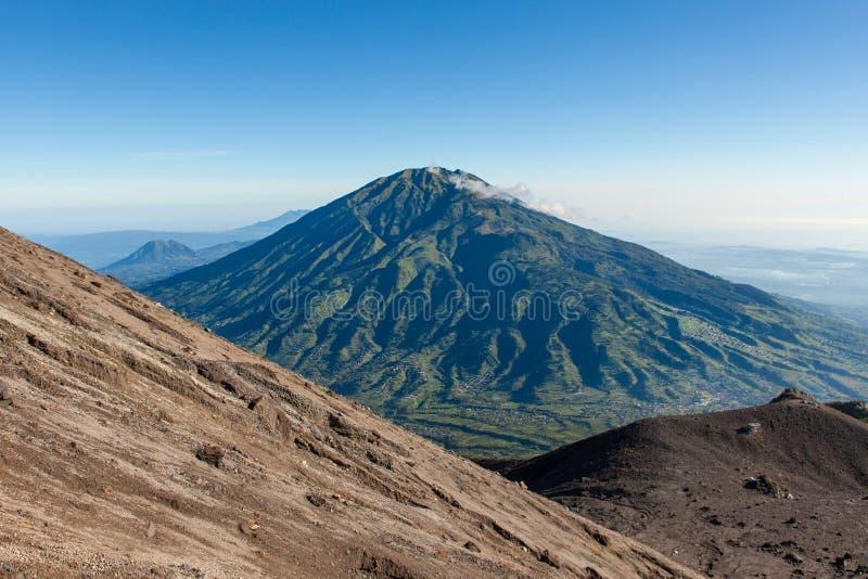 从Merapi山坡的绿色Merbabu山 免版税库存照片