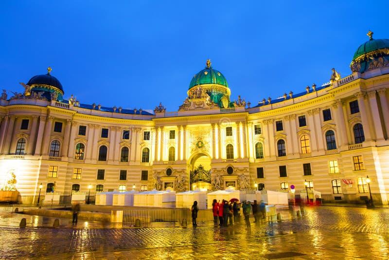 从Michaelerplatz看见的有启发性霍夫堡宫在晚上在维也纳,奥地利 免版税库存图片