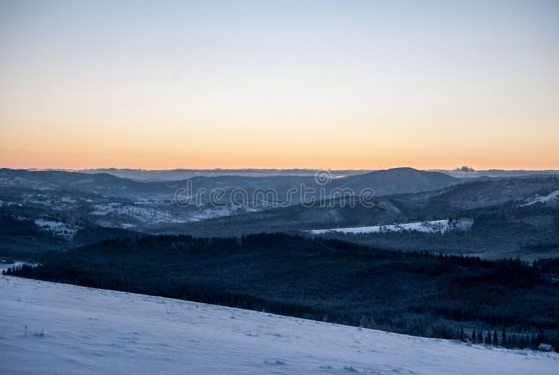 从Ochodzita小山的白天在冬天在Koniakow村庄上的Beskid Slaski山在有清楚的天空的波兰 免版税库存照片