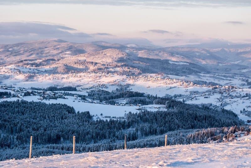 从Ochodzita小山的看法在西莱亚西Beskids山的Koniakow村庄上在波兰早晨结冰的冬天 免版税库存照片