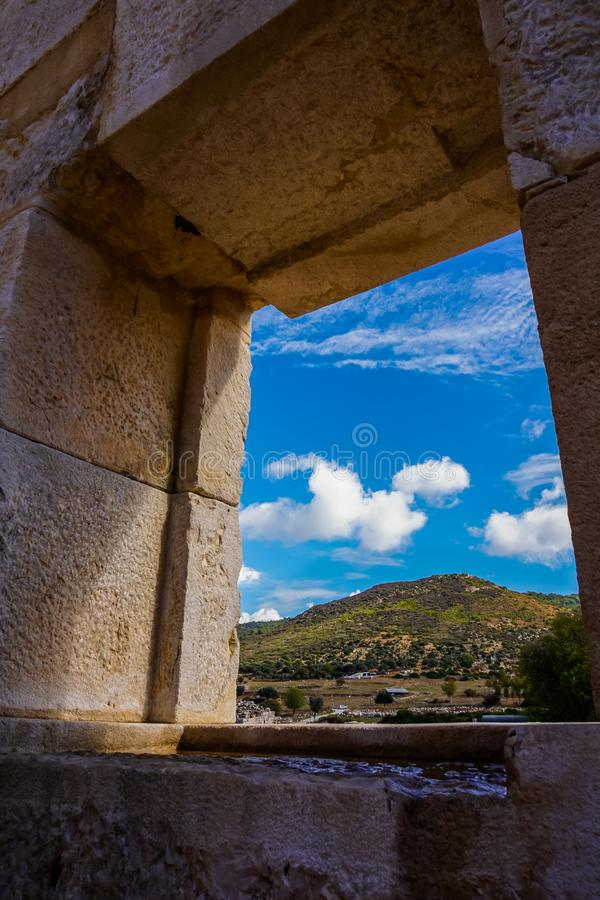 从Patara Bouleuterion在卡斯,安塔利亚,土耳其大厦窗口细节的山景  库存照片