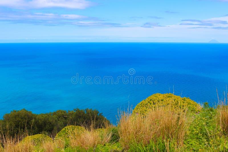 从Rocca二采取的第勒尼安海令人惊讶的观点切法卢,西西里岛,意大利 夺取与绿草和植物从岩石 库存照片