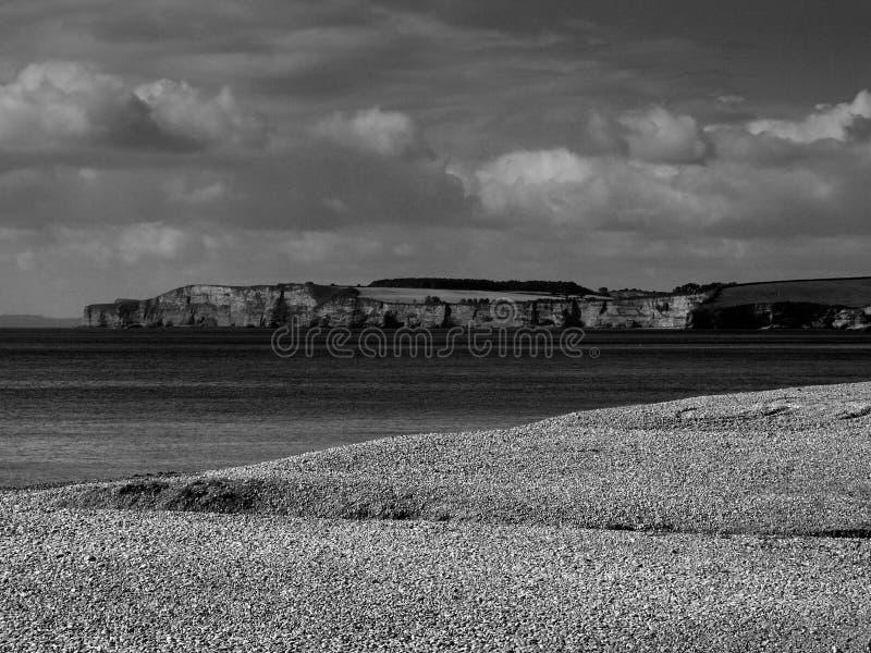 从Sidmouth的一个看法到Exmouth西部横跨石头、木瓦、海滩向西德文区和峭壁的 免版税库存照片